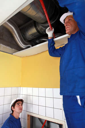 labourers: Two labourers checking ventilation system
