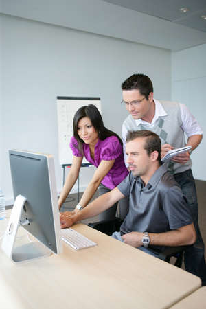Dynamic trio working at a desktop computer photo
