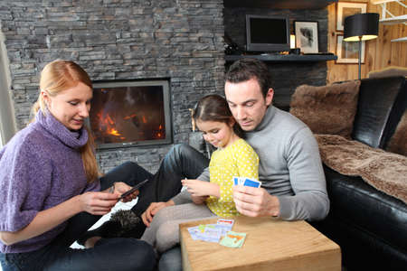 the warmth: Family gathered by the fire place playing cards Stock Photo