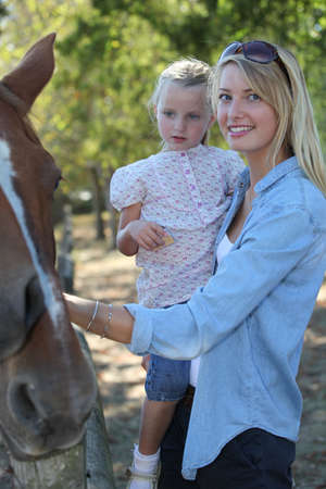 Mother and daughter stroking horse photo