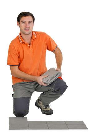 Man laying floor tiles photo