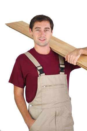 Carpenter carrying plywood photo