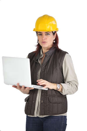 manual job: Female construction worker using her laptop Stock Photo