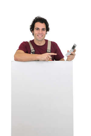 Handyman with a cellphone and a board left blank for your message photo