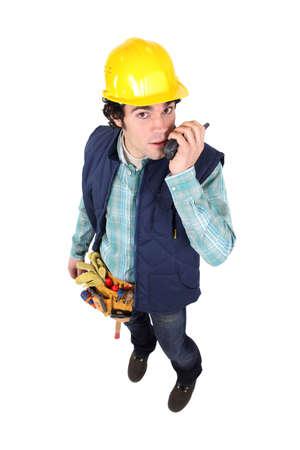 radio unit: Handyman speaking into radio unit Stock Photo