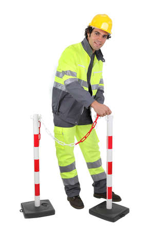 barrier rope: Construction worker putting up a barrier Stock Photo