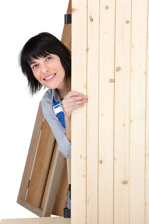 furtively: Woman hidden behind wooden plank Stock Photo