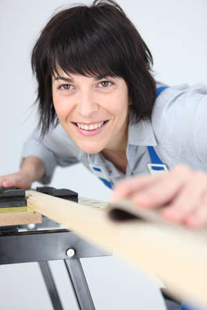 ebullient: Woman sanding a plank of wood