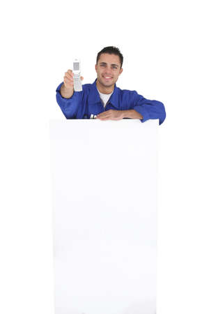 Tradesman holding a mobile phone over a blank sign and his tools photo