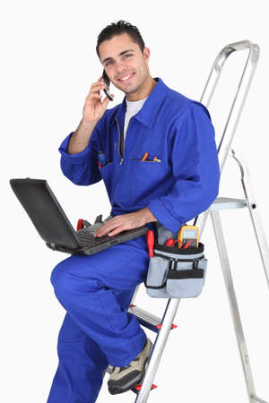 mobile telephone: Electrician chatting to customer on the phone Stock Photo