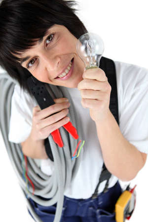 pep: Playful female electrician holding replacement light bulb