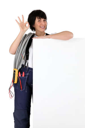 Female electrician with a board left blank for your message photo