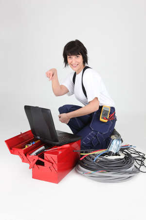 female electrician pointing at her laptop photo