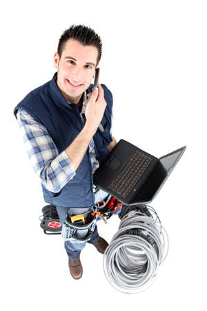 journeyman technician: electrician with laptop making a call