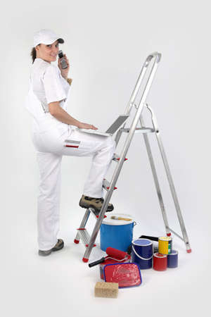 Female decorator with a phone and laptop photo