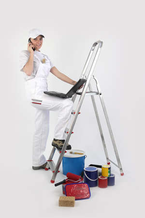 Painter posing by ladder with laptop and mobile photo