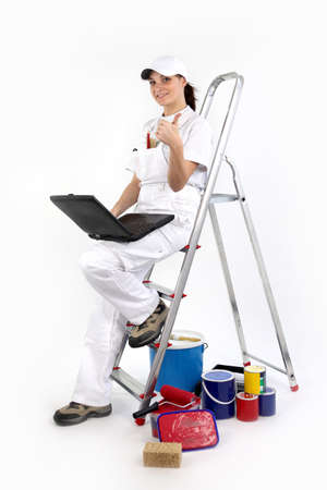 portrait of female painter decorator with laptop leaning against ladder photo