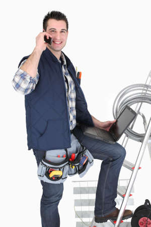 technician: Electrician with a cellphone and laptop Stock Photo