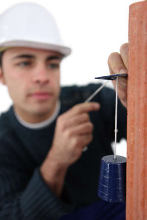 extent: craftsman taking measurements with a cord Stock Photo
