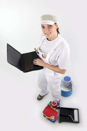 yourselfer: Female painter holding a computer Stock Photo