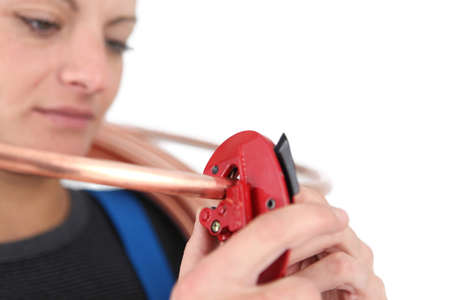 craftswoman: craftswoman cutting a cooper cable Stock Photo