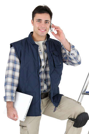 Tiler with mobile phone and equipment Stock Photo - 16037884