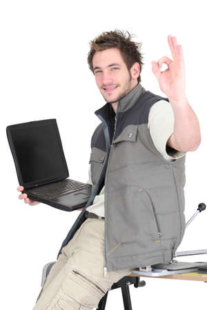 Tile cutter with laptop making OK gesture photo