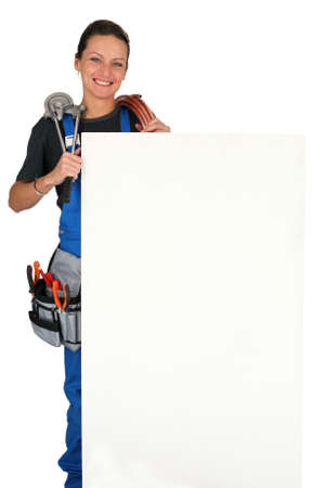 Female plumber with tools of the trade and a large board left blank for your message photo