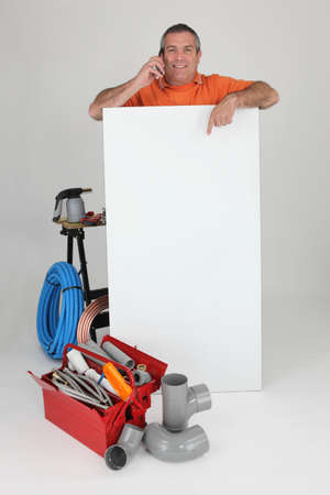 Plumber on the phone with a board left blank for your message photo