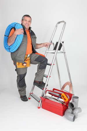 amateur: Hombre con escalera y herramientas de fontanería