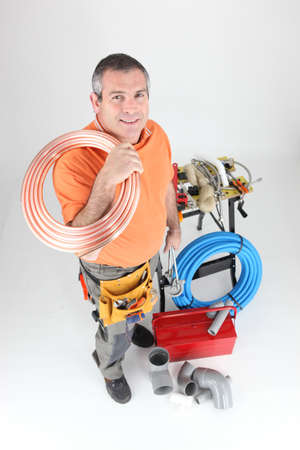 Plumber holding copper piping with various other materials photo