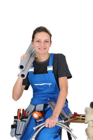 tradesperson: Female plumber with various tools and materials