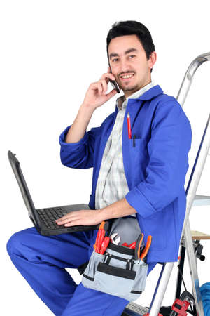 Plumber sat on step ladder holding mobile telephone photo