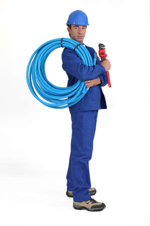 facing to camera: Man holding blue tube Stock Photo