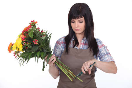 rolled up sleeves: Florist cutting stems off flowers Stock Photo