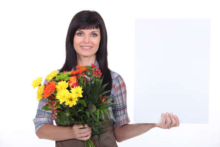 arranging: Florist with a bunch of flowers and a board left blank for your message Stock Photo