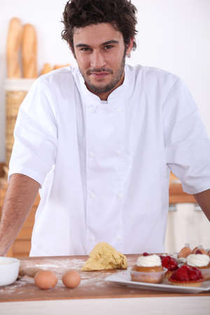 Male baker making sweet cakes photo