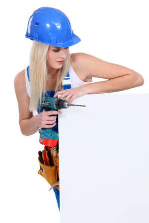 electric drill: Blond builder holding power drill and blank message board