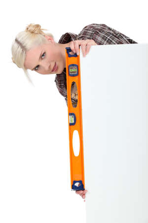 Woman with a spirit level and a board left blank for message or image Stock Photo - 16037705