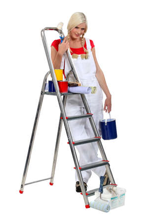 scaling ladder: Blond woman stood by ladder holding paint pot