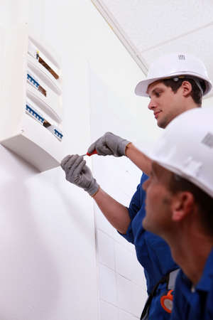 health and safety: Two electrical workers installing fuse box Stock Photo