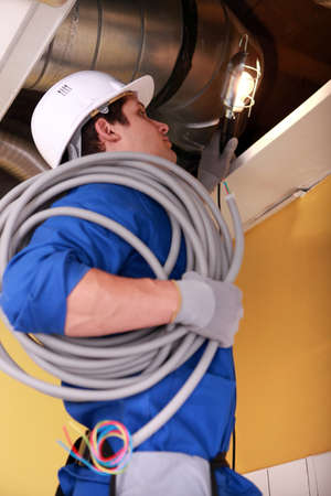 Electrician wiring an industrial loft space photo