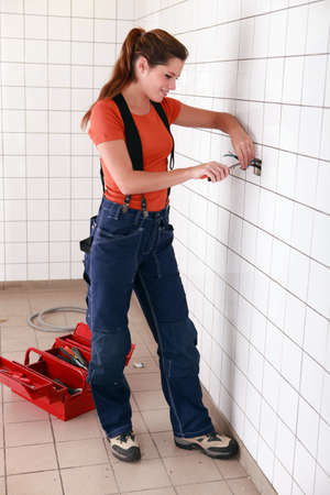 industrially: Female electrician working in bathroom Stock Photo