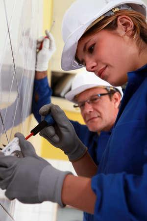 diligente: Mujer joven de instalar una toma de corriente Foto de archivo