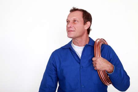 koperen leiding: Loodgieter met een reel van de koperen leiding Stockfoto