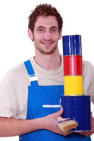 Young man in overalls with pots of paint in primary colors photo