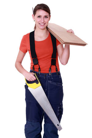 tradesperson: Woman carrying plywood and a saw