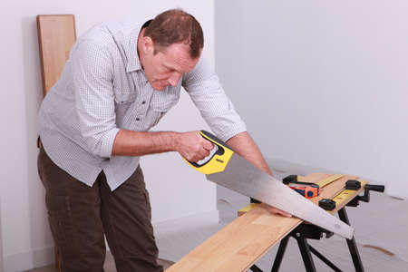 Man sawing a wooden floor photo