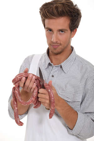 Young butcher cutting sausages on white background photo