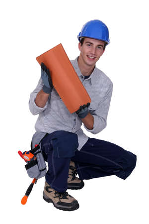 specialization: Craftsman crouching with tile Stock Photo
